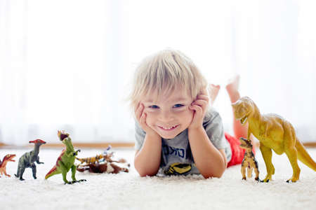 Blond toddler child, playing with dinosaurs at home, nice soft back light Фото со стока - 151122092