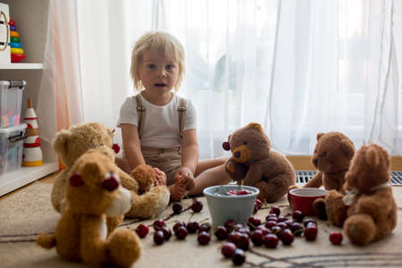 Toddler blond child, cute boy, eating cherries with teddy bears at home Фото со стока - 151058310