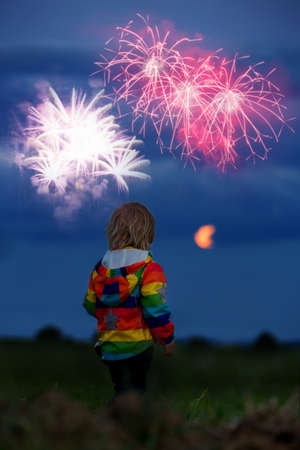 Happy toddler boy, child, looking at fireworks for 4th of July in a fiel, full moon rising up in the sky