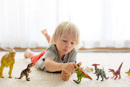 Blond toddler child, playing with dinosaurs at home, nice soft back light