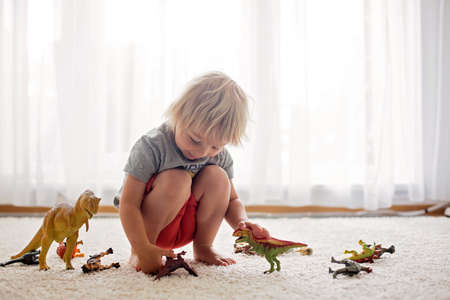 Blond toddler child, playing with dinosaurs at home, nice soft back light Фото со стока - 151122095