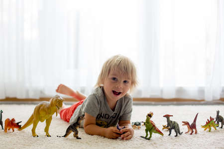 Blond toddler child, playing with dinosaurs at home, nice soft back light Фото со стока - 151122102