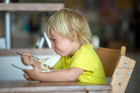 Cute blond boy, child eating spaghetti, crying with tantrum at home