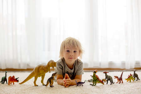 Blond toddler child, playing with dinosaurs at home, nice soft back light Фото со стока - 151122107