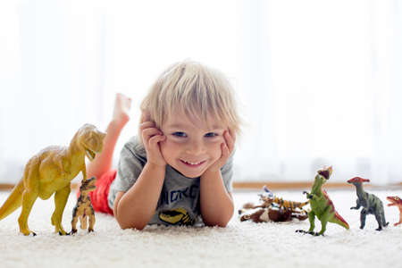 Blond toddler child, playing with dinosaurs at home, nice soft back light Фото со стока - 151122108
