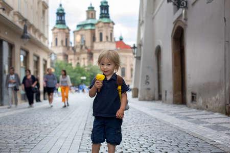 Cute child, boy, visiting Prague after the quarantine Covid 19, eating ice cream, empty streets Фото со стока - 151122270