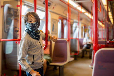 Child, boy, wearing protective mask in underground. Sid in subway in Prague, wearing mask Фото со стока - 151122272