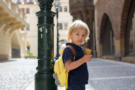 Cute child, boy, visiting Prague after the quarantine Covid 19, eating ice cream, empty streets Фото со стока - 151122286