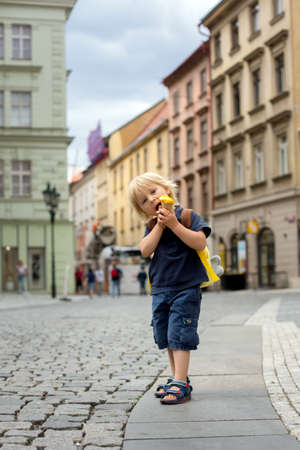 Cute child, boy, visiting Prague after the quarantine Covid 19, eating ice cream, empty streets Фото со стока - 151122293