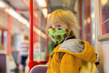 Child, boy, wearing protective mask in underground. Sid in subway in Prague, wearing mask