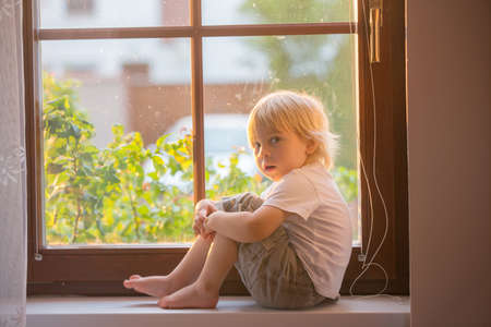 Abandoned little toddler boy, sitting sad on a window shield, looking outside at the sunset Фото со стока - 151069318