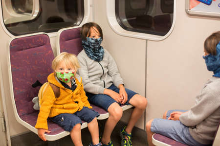 Child, boy, wearing protective mask in underground. Sit in subway in Prague, wearing mask Фото со стока