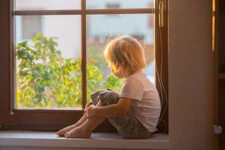 Abandoned little toddler boy, sitting sad on a window shield, looking outside at the sunset