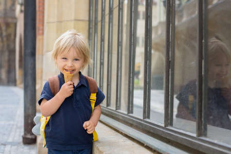 Cute child, boy, visiting Prague after the quarantine Covid 19, eating ice cream, empty streets