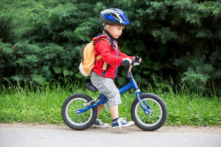 Cute toddler boy with blue helmet, riding balance bike on the street, blurred background Фото со стока - 151069493