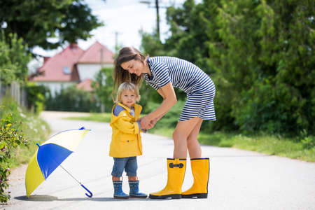 Mother and toddler child, boy, playing in the rain, wearing boots and raincoats Фото со стока - 151069525