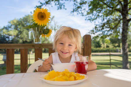 Child, toddler boy, having breakfast in the morning, sitting on porch of camping van, traveling summer time, family vacation
