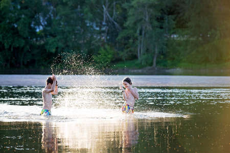 Beautiful portrait of children in lake, kids playing in the water on sunset, summertime