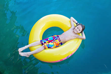 Sweet child, preschool boy. lying on floating ring in lake, pictures from above