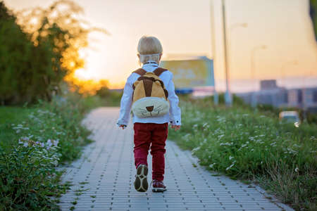 Cute blond preschool child, wearing medical mask dressed in uniform, going to preschool for the first time after summer