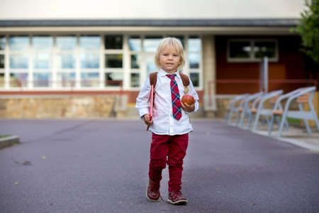 Preschool blond child, cute boy in uniform, hodling apple and book, going in preschool for the first time after summer vacation