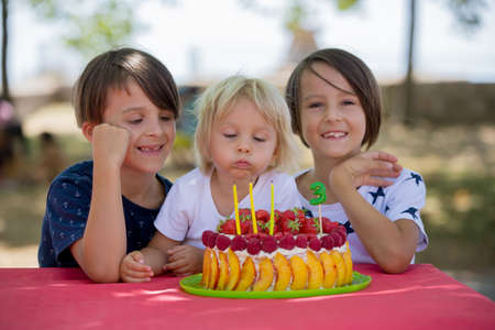 Sweet little blond toddler boy, celebrating his third birthday in a park, outdoors