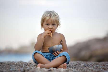 Cute boy, child, eating spaghetti on the beach, enjoying dinner outdoors