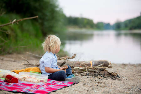 Toddler boy, child having picnic with his family and campfire in the evening near river summertime