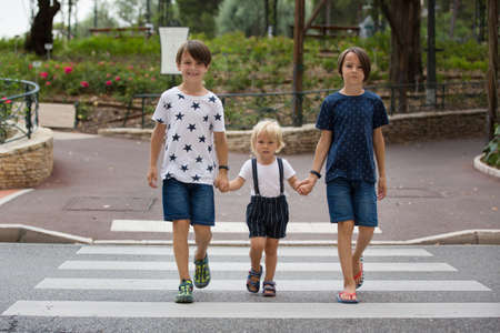 Children, boy brothers, siblings holding hands and crossing crosswalk on the street, summertime Фото со стока