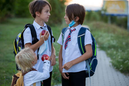 School children, boys wearing medical masks, going back to school after the summer vacation, kids going to school Фото со стока