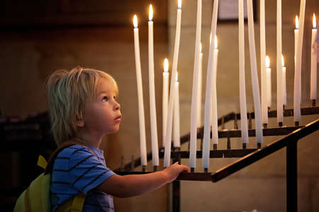 Little toddler boy, praying in chapel with candles in front of him Фото со стока
