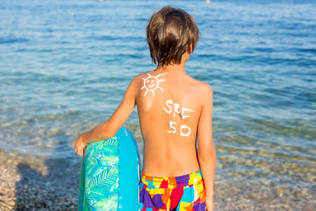 Child, preteen boy with sun protection cream on his back on the beach, holding inflatable ring