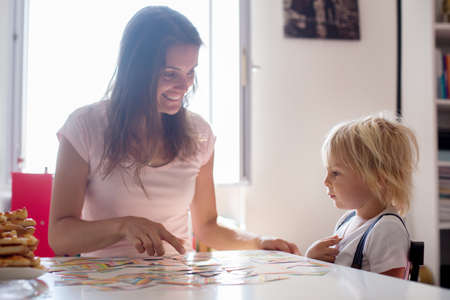 Mother, teaching her child toddler boy the alphabet and numbers, educating him
