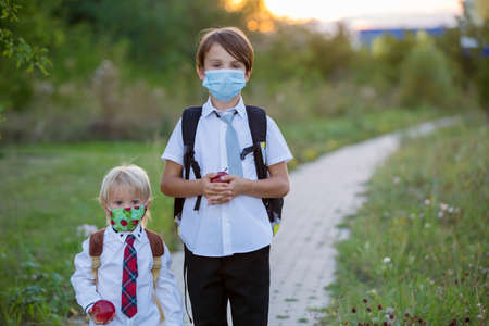School children, boys wearing medical masks, going back to school after the summer vacation, kids going to school