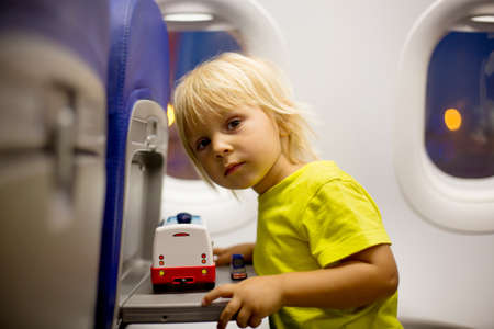 Toddler boy, child boarding on the airplane, sitting and waiting for departure, playing with toys, smiling happily