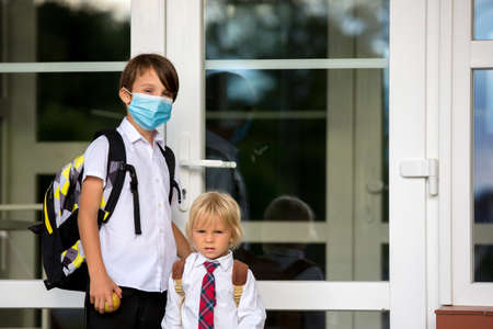 School child, boy wearing medical masks, going back to school after the summer vacation, kid going to school autumntime