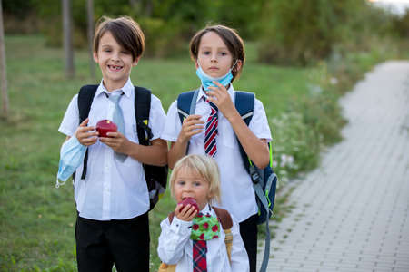 School children, boys wearing medical masks, going back to school after the summer vacation, kids going to school autumntime Фото со стока