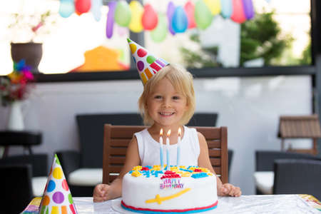 Adorable happy child, little kid boy celebrating his birthday at home with balloons, siblings and colorful homemade cake