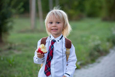 Preschool blond child, cute boy in uniform, holding apple, going in preschool for the first time after summer vacation