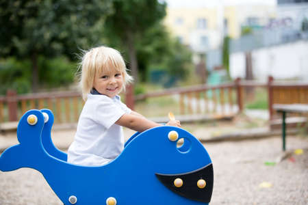 Cute toddler childplaying on the playground, rocking on blue fish rocking swing Фото со стока