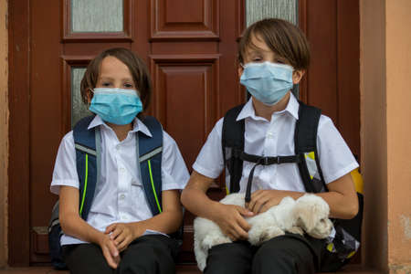 School children, boys, going back to school after the summer vacation, kids going to school wearing medical mask due to coronavirus COVID 19