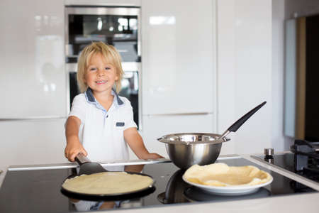 Cute toddler child, blond boy, making pancake in kitchen, eating them