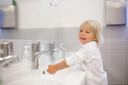 Little preschool child, blond boy, washing hands in bathroom in kindergarden, hygiene habits Фото со стока