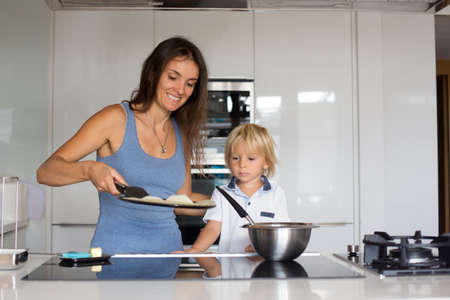 Cute toddler child and mom, mother and blond boy, making pancake in kitchen, eating them Фото со стока