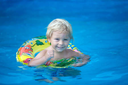 Cute toddler child, boy, swimming in pool with board and inflatable ring Фото со стока