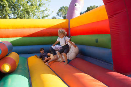 Children, boys, playing jumping on colorful trampoline in park
