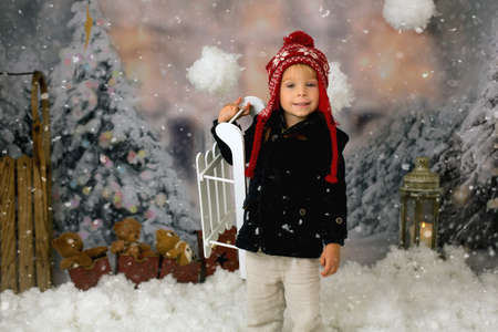 Cute boy, preschool child, playing in the snow outdoors, studio shot