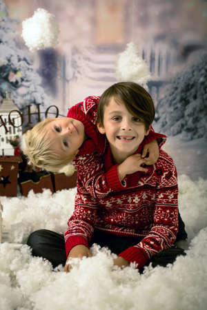 Cute boys, boy brothers, beautiful children, playing in the snow outdoors, Christmas concept studio shot