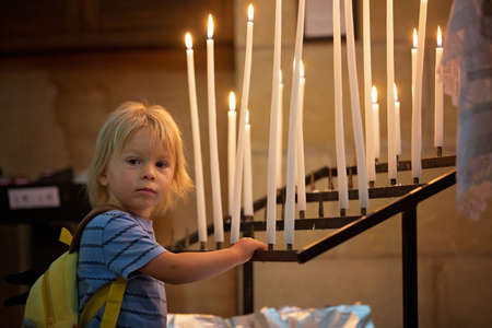 Little toddler boy, praying in chapel with candles in front of him Stock Photo