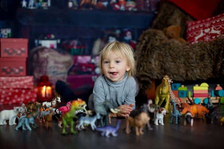 Sweet blonde toddler boy, playing with plastic animals and dinosaurs at home, christmas decoration around him
